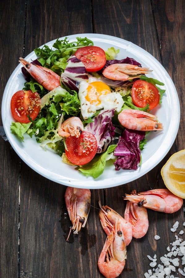 Zdrowa garneli i Arugula sałatka z pomidorami na drewnianym stole zdjęcia stock