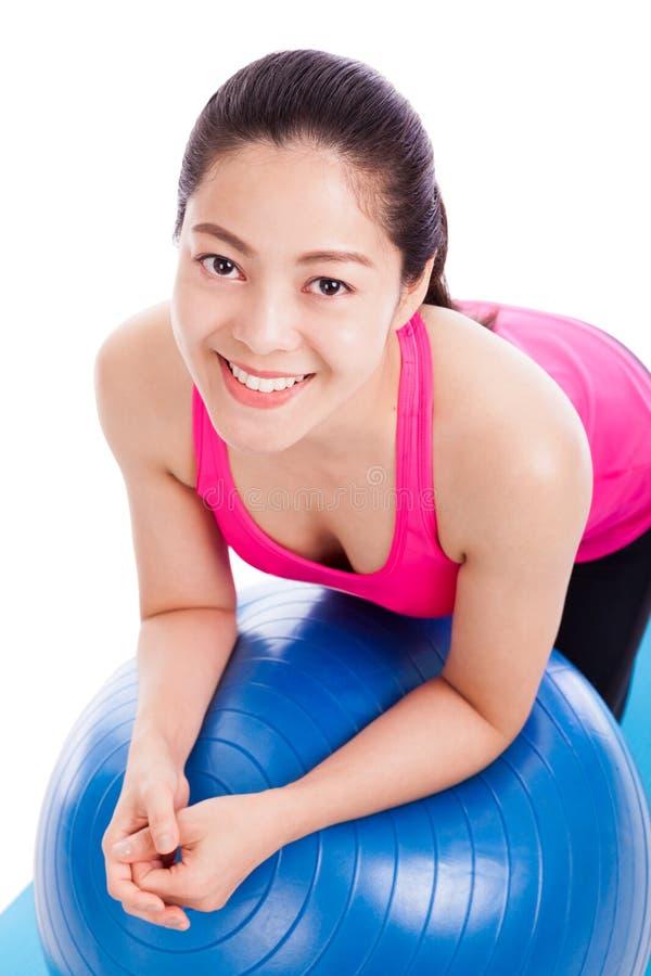 Zdrowa kobieta - dziewczyny uśmiechnięta i oparta sprawności fizycznej piłka odizolowywał o zdjęcia stock