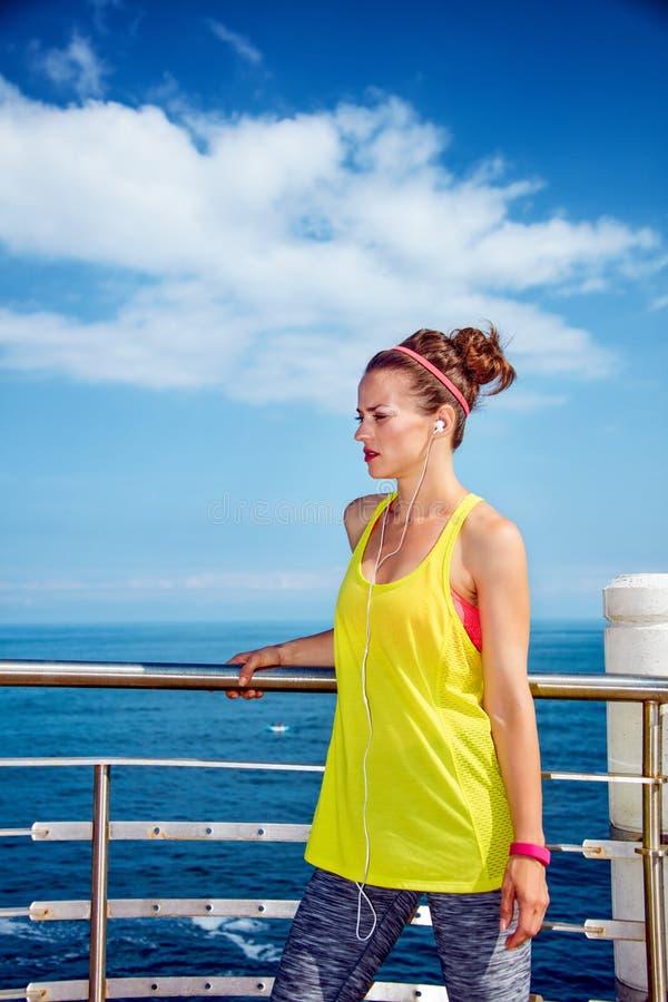 Zdrowa kobieta słucha muzyka przy bulwarem w sprawność fizyczna stroju obrazy stock