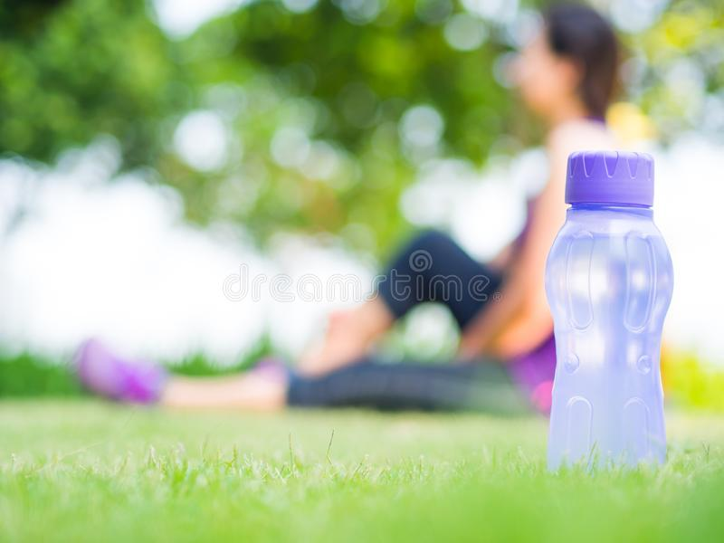 Zdrowa kobiety atleta jest odpoczynkowa na trawie Ostrość na butelce woda zdjęcia royalty free