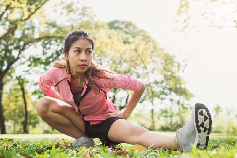 Zdrowa młoda azjatykcia kobieta ćwiczy przy parkiem Dysponowana młoda kobieta robi stażowemu treningowi w ranku zdjęcie royalty free