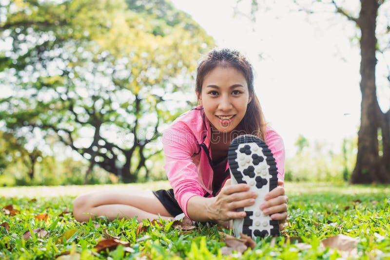Zdrowa młoda azjatykcia kobieta ćwiczy przy parkiem Dysponowana młoda kobieta robi stażowemu treningowi w ranku obrazy stock