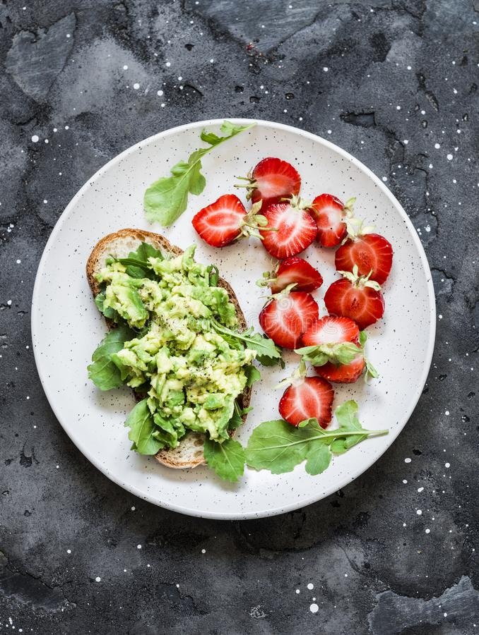Zdrowa przekąska, śniadanie - ściska z avocado i świeżymi truskawkami na ciemnym tle, odgórny widok fotografia stock