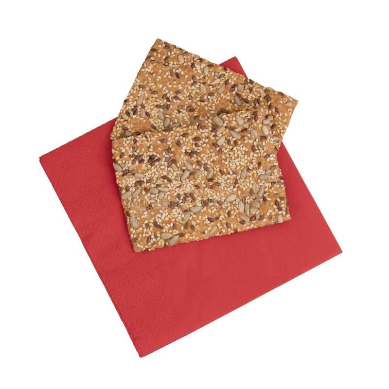 Zdrowa przekąska, wholemeal, wholewheat krakersy z słonecznikiem, linseed i sezamowi ziarna, Na czerwień papieru serviette, pielu fotografia stock