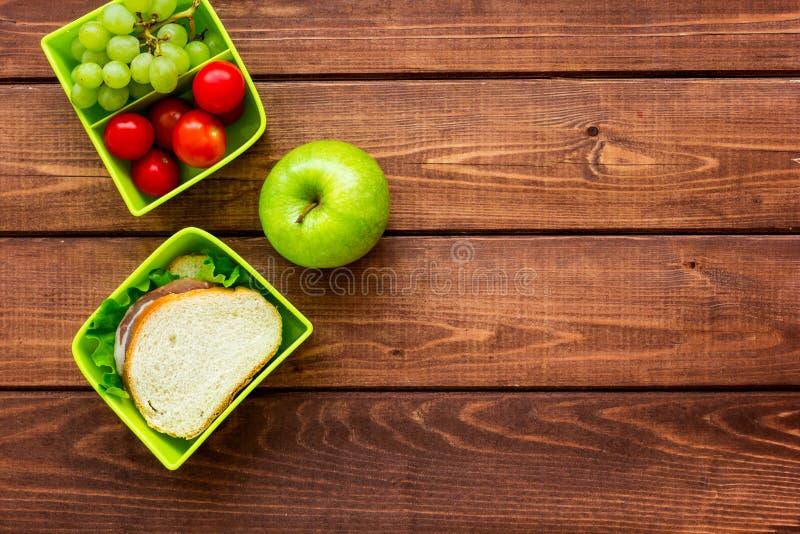 Zdrowa przerwa z jabłkiem, winogronem i kanapką w lunchbox na domu stołu mieszkania nieatutowym egzaminie próbnym, fotografia stock