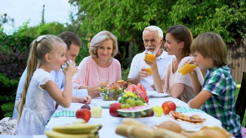 Zdrowa rozochocona rodzina pije nawitaminującego świeżego sok, świętuje tradycje zdjęcie royalty free