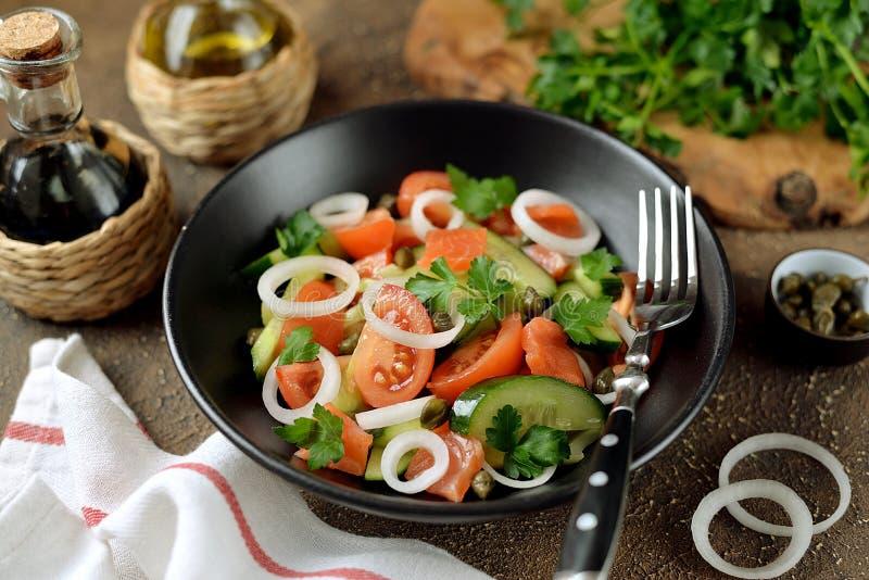 Zdrowa sałatka czereśniowi pomidory, ogórek, seler, cebule, kapary i pietruszka z solonym łososiem, obraz stock
