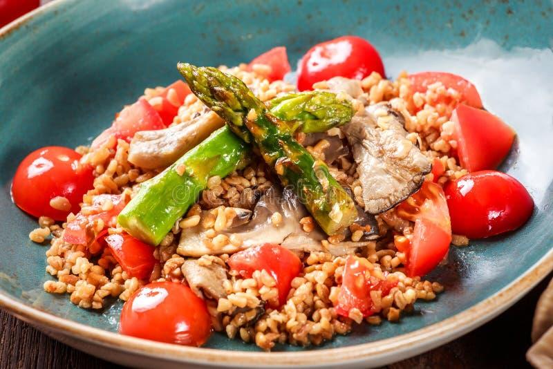 Zdrowa sałatka jęczmienna owsianka z asparagusem, pomidorami i pieczarkami na talerzu, Weganinu jedzenie obraz royalty free