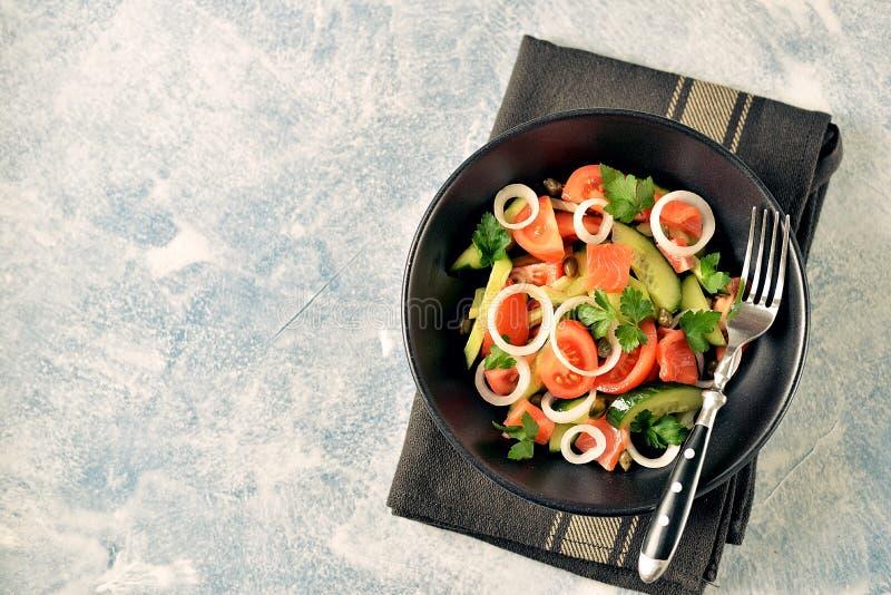 Zdrowa sa?atka czere?niowi pomidory, og?rek, seler, cebule, kapary i pietruszka z solonym ?ososiem, zdjęcie stock
