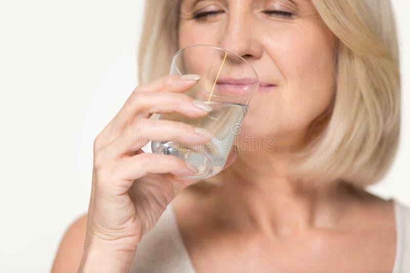 Zdrowa spragniona starsza starej kobiety woda pitna odizolowywająca na tle zdjęcie stock