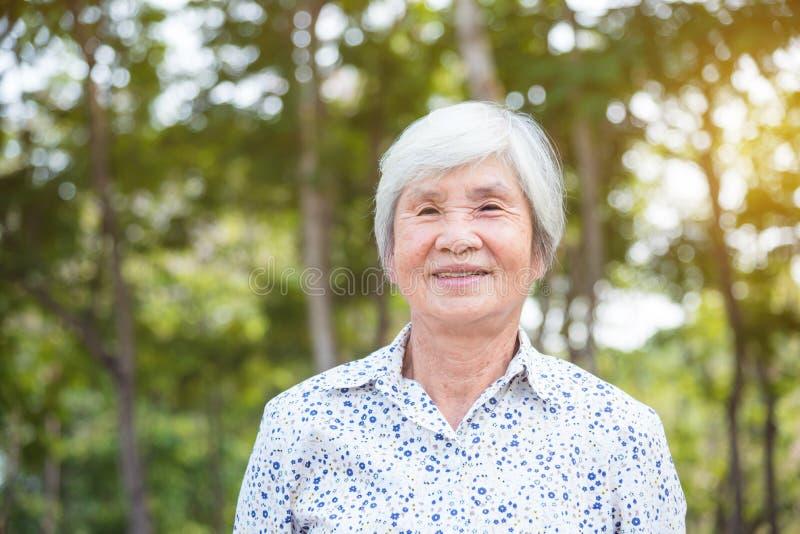 Zdrowa starsza kobieta ono uśmiecha się w parku obrazy stock