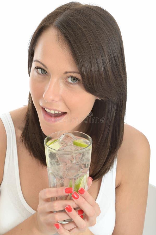 Zdrowa Szczęśliwa Atrakcyjna Naturalna młoda kobieta Trzyma szkło woda z Dojrzałym wapnem i kostkami lodu obraz royalty free
