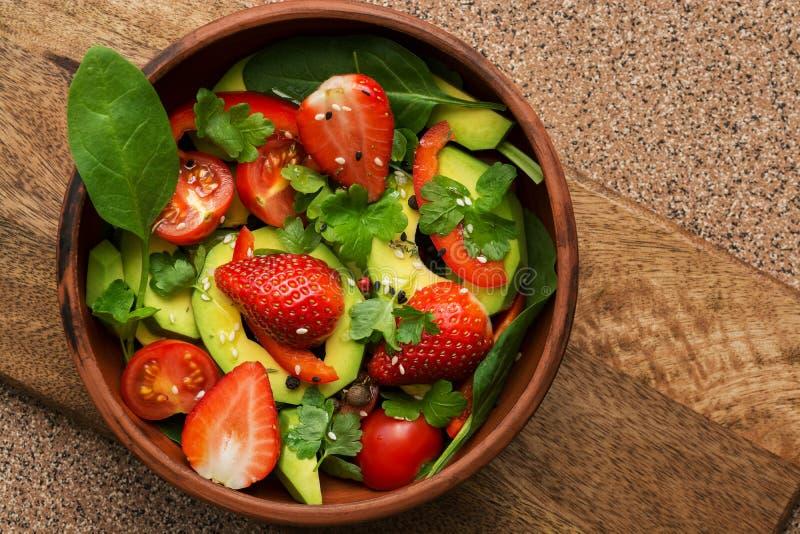 Zdrowa weganin sałatka avocado, szpinak, słodcy pieprze, truskawki, czereśniowi pomidory i pietruszka -, zdrowy pojęcia łasowanie obraz stock
