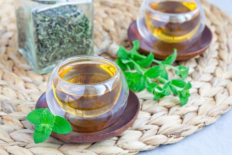 Zdrowa ziołowa nowa herbata w orientalnej szklanej filiżance z świeżą miętówką i herbacianym słojem na tle zdjęcia royalty free