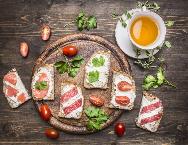 Zdrowe foods kanapki z czerwieni ryba, czereśniowymi pomidorami i salami na tnącej desce, filiżanka herbata z macierzanką na drew zdjęcie stock