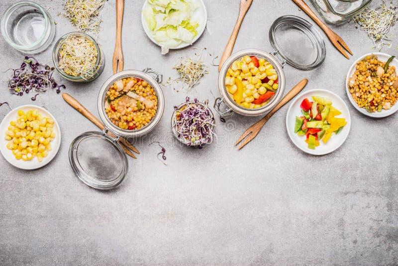 Zdrowe jarskie kukurydzane sałatki Różnorodna sałatka w szklanych słojach na szarość dryluje tło zdjęcie royalty free