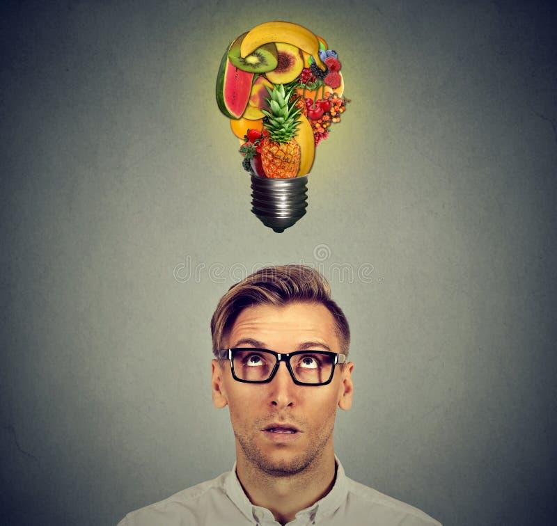 zdrowe jeść Mężczyzna przyglądający przy owocową żarówką up zdjęcie royalty free