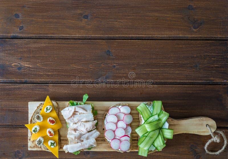 Zdrowe otwarte kanapki z warzywami, og?rkowej rzodkwi pastrami cheddaru indyczym serem i mi?kkim serem na drewnianym tle, zdjęcia royalty free