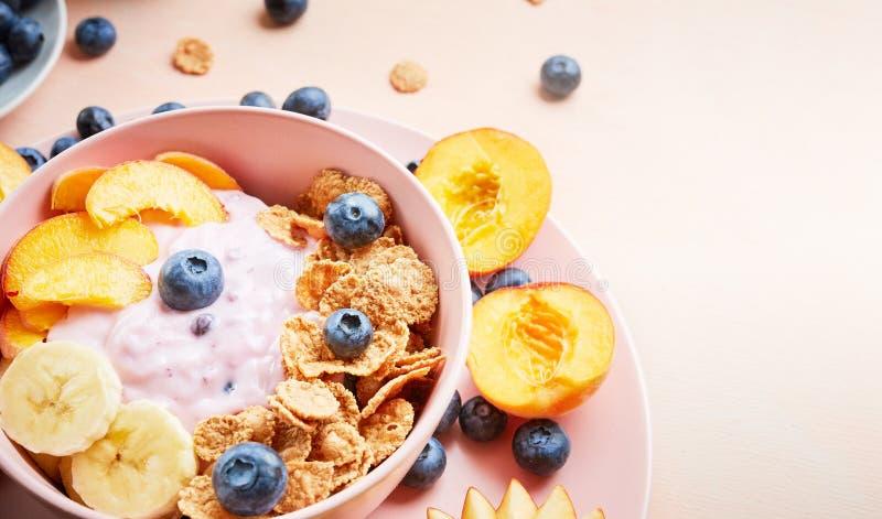 Zdrowego śniadaniowego pucharu jagodowy grecki jogurt z czarnymi jagodami, bananem i płatkami na różowym drewnianym stole frefh, zdjęcia royalty free