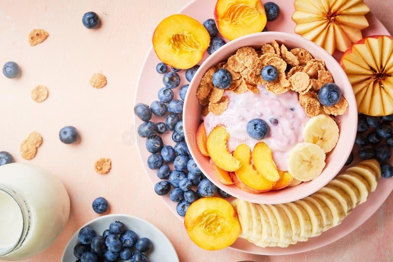 Zdrowego śniadaniowego pucharu jagodowy grecki jogurt z czarnymi jagodami, bananem i płatkami na różowym drewnianym stole frefh, obraz stock