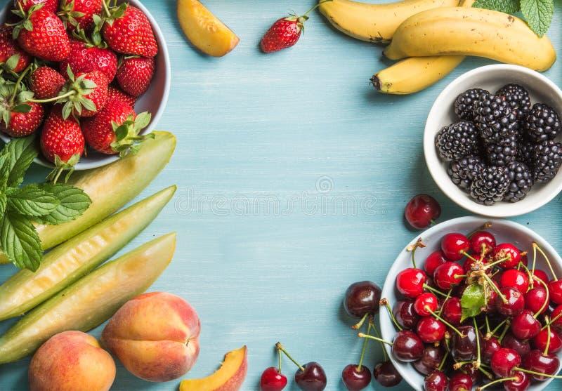 Zdrowego lata owocowa rozmaitość Słodkie wiśnie, truskawki, czernicy, brzoskwinie, banany, melonów plasterki i nowi liście, fotografia royalty free