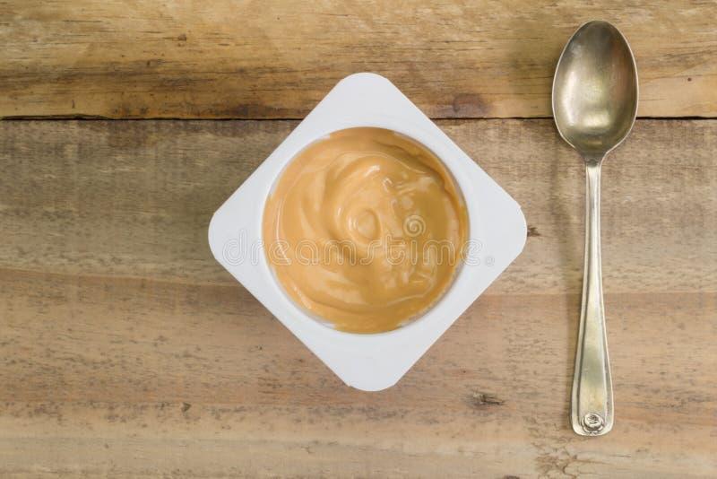 Zdrowego naturalnego karmelu śmietankowy jogurt w małym białym plastikowym cu fotografia royalty free