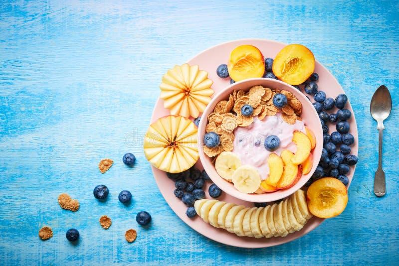 Zdrowego ?niadaniowego pucharu jagodowy grecki jogurt z czarnymi jagodami, bananem i p?atkami na b??kitnym drewnianym stole frefh zdjęcie stock