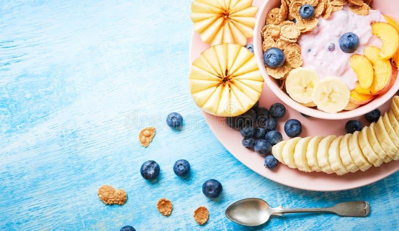 Zdrowego ?niadaniowego pucharu jagodowy grecki jogurt z czarnymi jagodami, bananem i p?atkami na b??kitnym drewnianym stole frefh zdjęcie royalty free