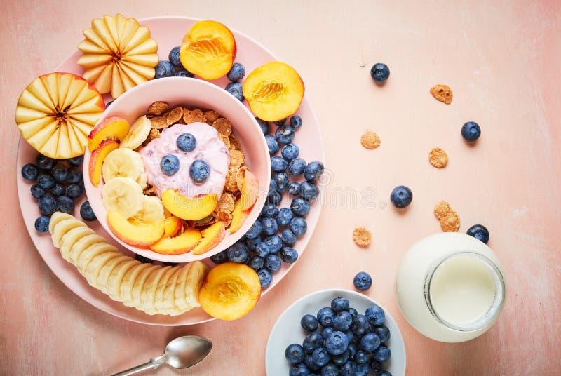 Zdrowego ?niadaniowego pucharu jagodowy grecki jogurt z czarnymi jagodami, bananem i p?atkami na r??owym drewnianym stole frefh, obrazy stock