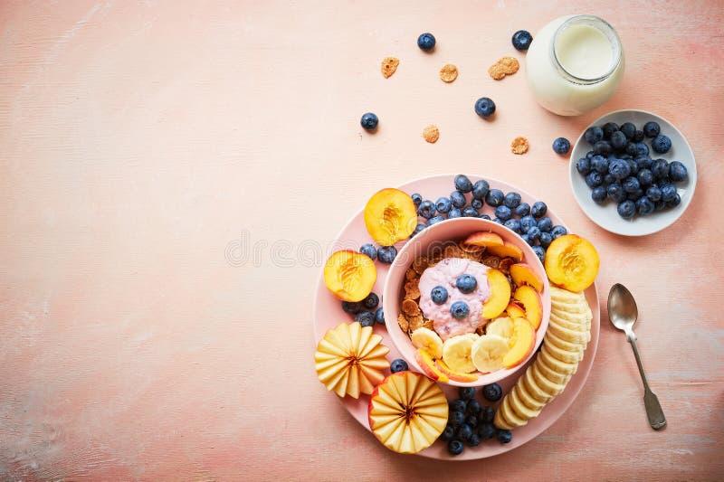 Zdrowego ?niadaniowego pucharu jagodowy grecki jogurt z czarnymi jagodami, bananem i p?atkami na r??owym drewnianym stole frefh, obraz royalty free