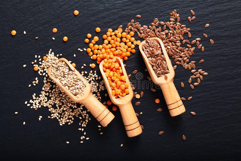 Zdrowego odżywiania karmowy len, sezam i pomarańcze soczewicy ziarna w bambusowej miarce z kopii przestrzenią, obrazy stock