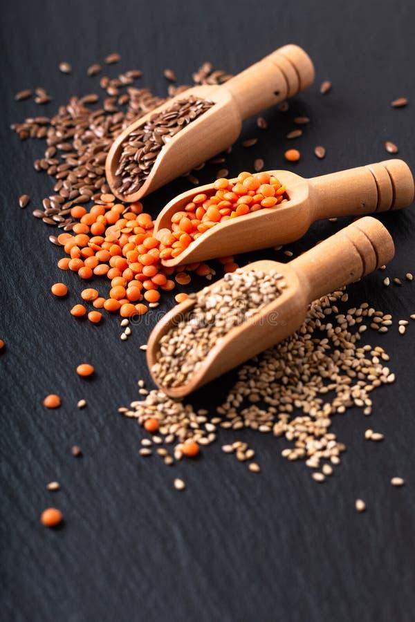 Zdrowego odżywiania karmowy len, sezam i pomarańcze soczewicy ziarna w bambusowej miarce z kopii przestrzenią, fotografia royalty free