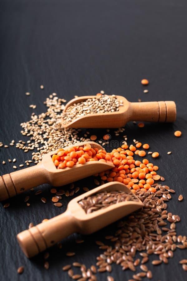 Zdrowego odżywiania karmowy len, sezam i pomarańcze soczewicy ziarna w bambusowej miarce z kopii przestrzenią, obraz stock