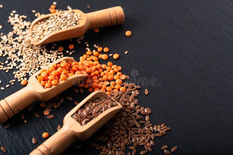 Zdrowego odżywiania karmowy len, sezam i pomarańcze soczewicy ziarna w bambusowej miarce z kopii przestrzenią, zdjęcie royalty free