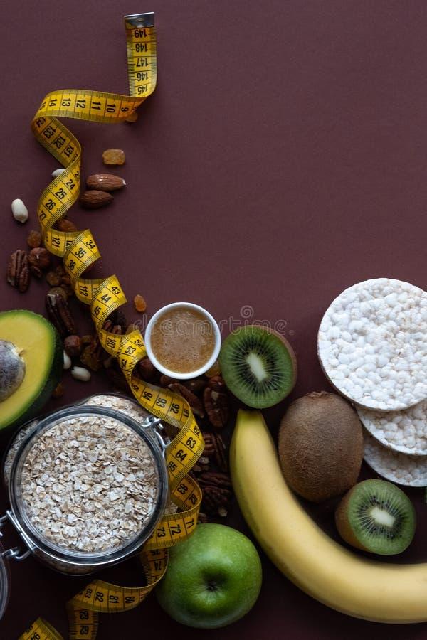 Zdrowi śniadaniowi ingrediens Domowej roboty granola w otwartym szklanym słoju, miód, dokrętki, owoc, żółty pas ruchu na brązu tl zdjęcie royalty free