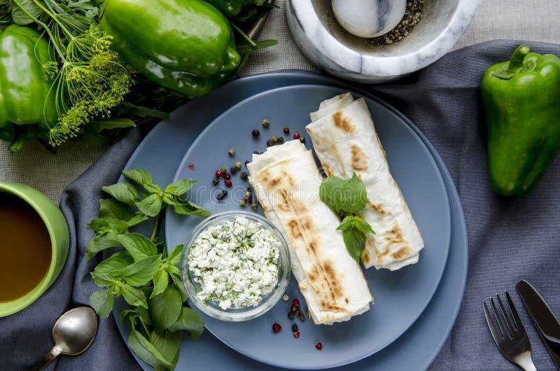Zdrowi śniadanie zieleni warzywa Pita chleb z serem i koperkowy kłamstwo na round szarość talerzach obok zieleni i filiżanka kawy obrazy stock