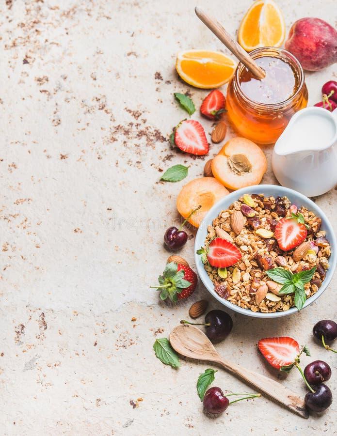 Zdrowi Śniadaniowi składniki Owsa granola w pucharze z dokrętek, truskawkowych i nowych liśćmi, miotacz, miód w słoju, świeżym obrazy royalty free
