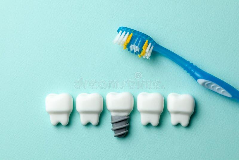 Zdrowi biali zęby i wszczepy na zieleni wybijają monety tło z toothbrush obraz stock