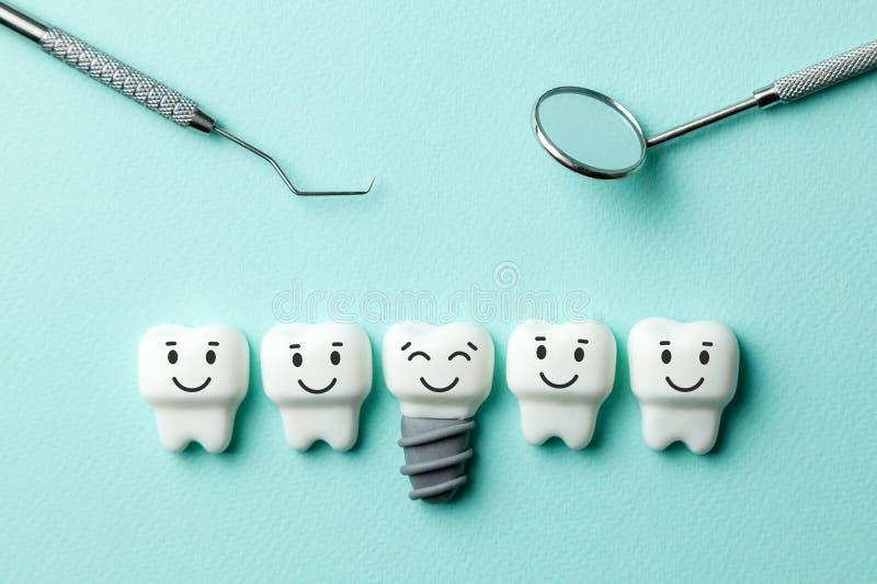 Zdrowi biali zęby i wszczepy są uśmiechnięci przeciw zieleni mennicy tłu i dentystów narzędzia odzwierciedlają, haczą, zdjęcie stock