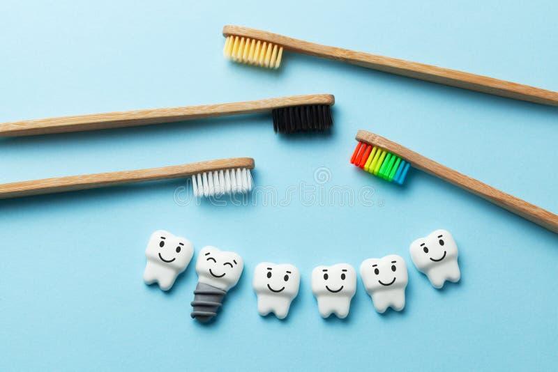 Zdrowi biali z?by i wszczepy s? u?miechni?ci na b??kitnym tle z toothbrush zdjęcia royalty free