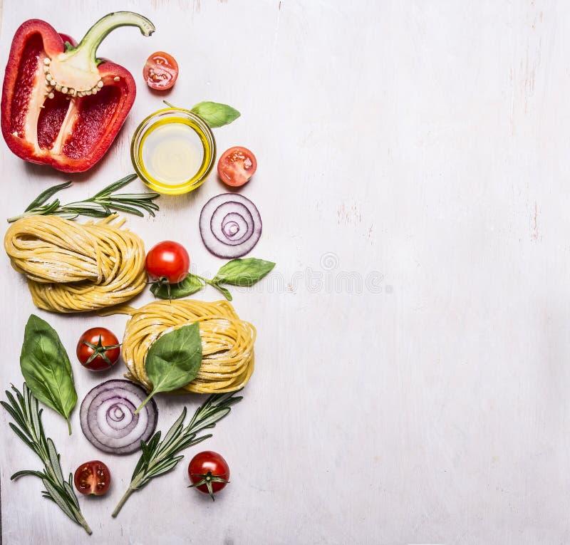 Zdrowi foods, jarskiego pojęcia kulinarny makaron z mąką, warzywa, olej i ziele, cebula, pieprz na drewnianym nieociosanym tle fotografia royalty free