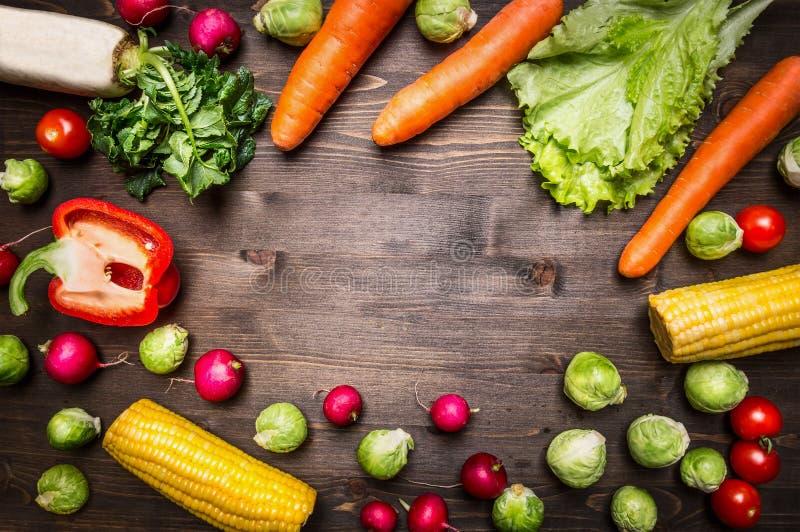 Zdrowi foods, kucharstwo i jarosza pojęcia pieprze, marchewki, daikon, sałata, rzodkwie, kukurudza, rozmaryn umieszczają tekst, r obrazy royalty free