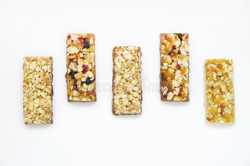 Zdrowi granola bary z dokrętkami, ziarnami i wysuszonymi owoc na białym pieczeniu, tapetują Odgórny widok zdjęcia stock