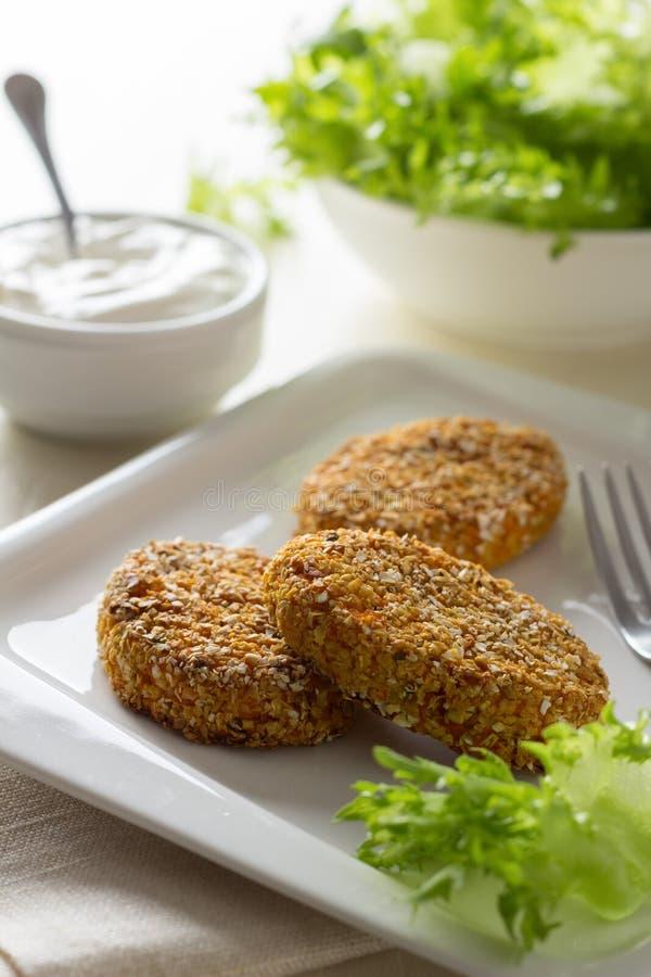 Zdrowi jarzynowi cutlets z marchewką, wysuszonymi morelami migdały i ziele breaded w owsa otręby, zdjęcie stock