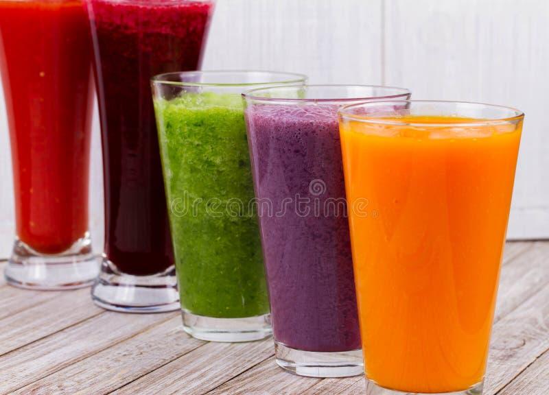Zdrowi Kolorowi Smoothies z owoc i warzywo Przeciw Nieociosanemu Drewnianemu tłu zdjęcie stock