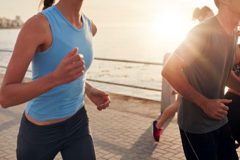 Zdrowi młodzi ludzie biega wpólnie w mieście zdjęcia stock
