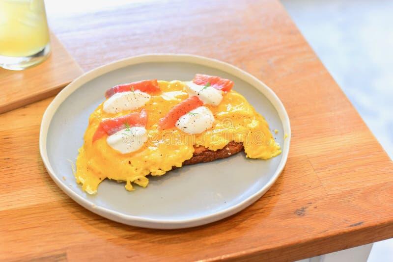 Zdrowi Rozdrapani jajka z Uwędzonym łososiem na grzance obrazy royalty free