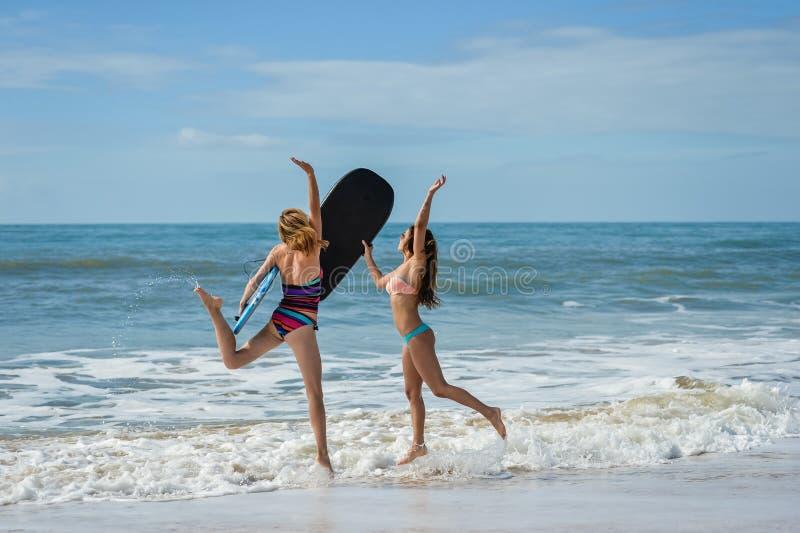 Zdrowi sportowi surfingowiec dziewczyny przyjaciele z dysponowanymi bodies trzyma bodyboards obraz stock