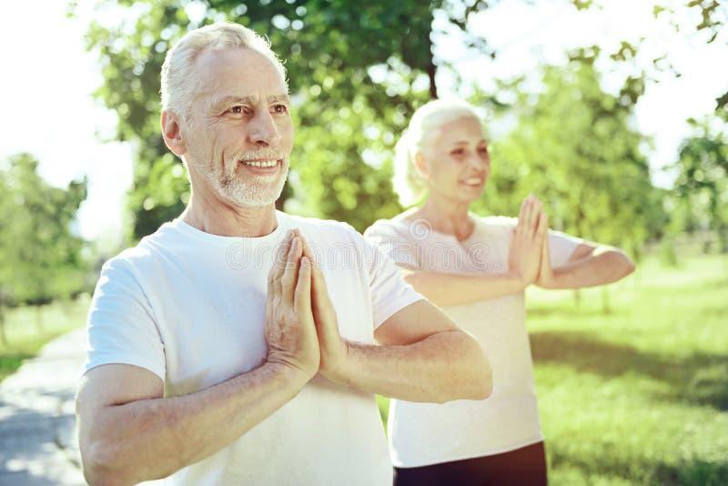 Zdrowi starzejący się ludzie ćwiczy joga wpólnie obraz royalty free