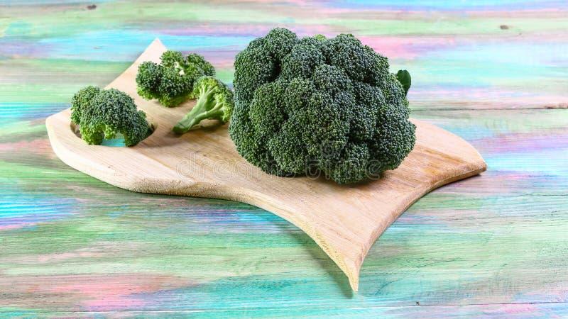 Zdrowi Zieleni Organicznie Surowi brokułów Florets Przygotowywający dla Gotować Wiązka świezi zieleni brokuły na drewnianej desce zdjęcia royalty free